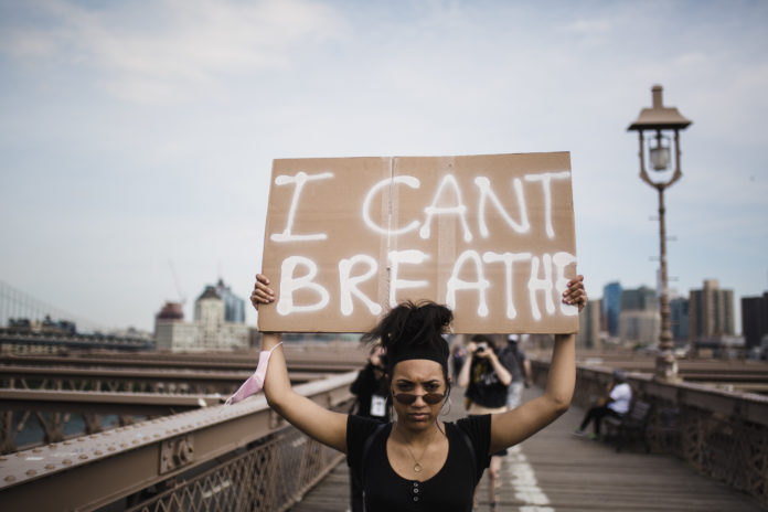 Femme portant un panneau 'I can't breath'